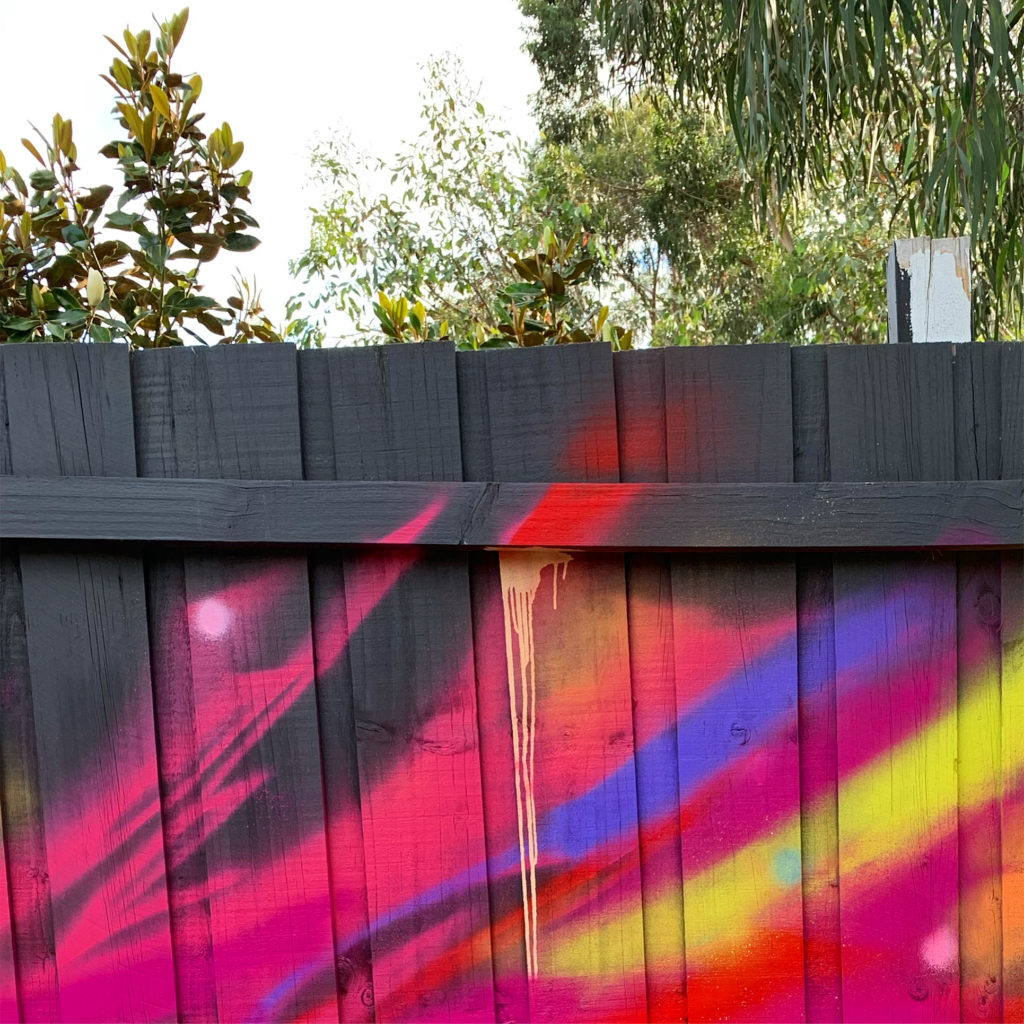 Bright colours spray painted onto a dark fence