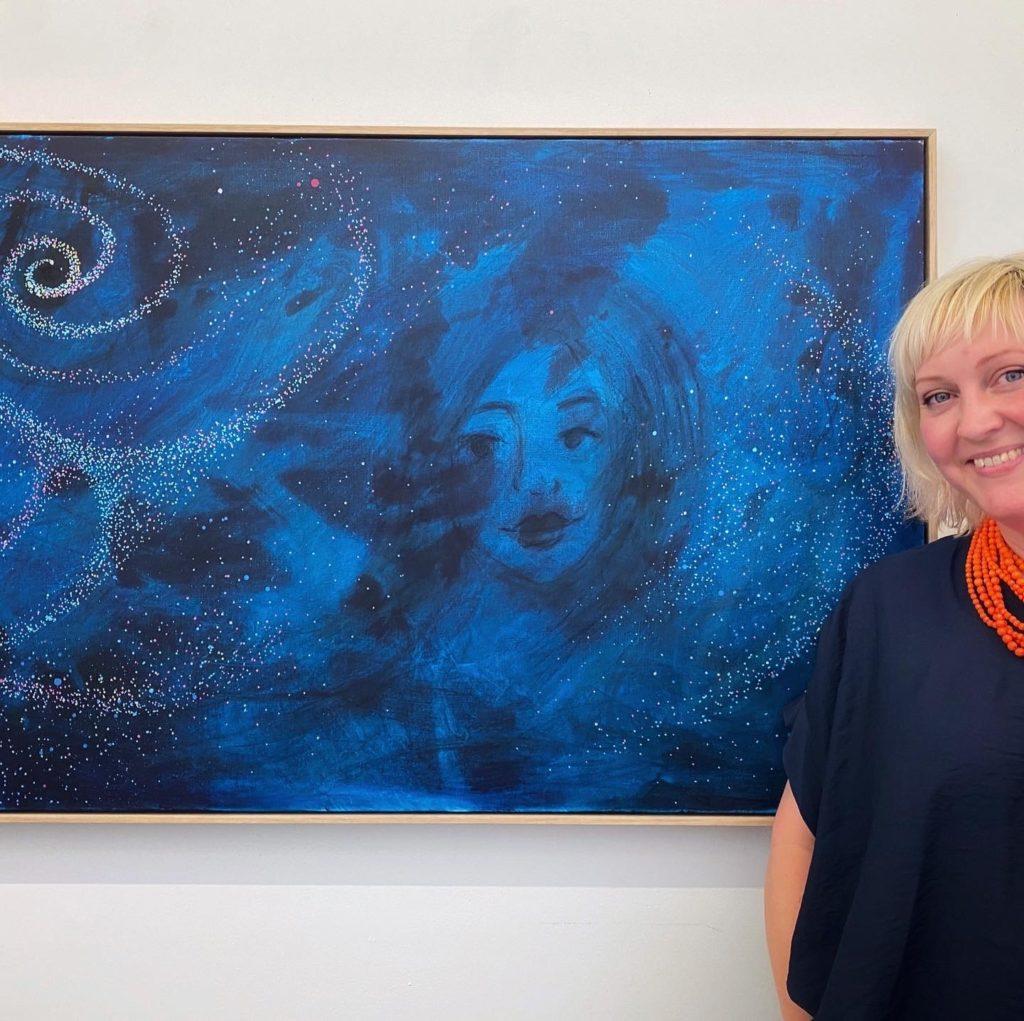 Jasmin standing next to her artwork