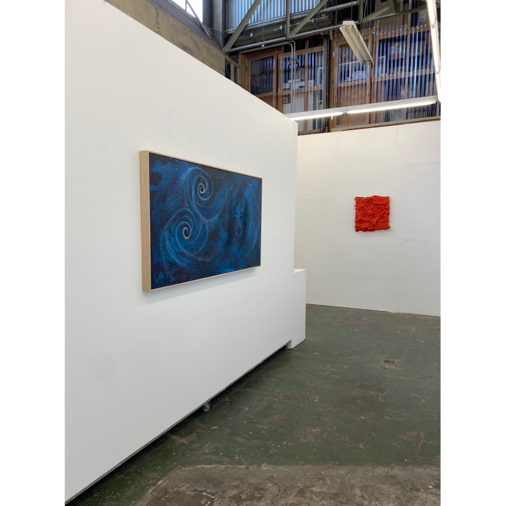 A large blue painting inside a white art gallery space